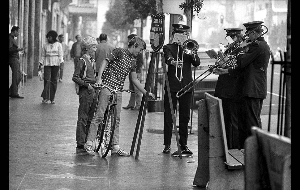 Dec. 20, 1971: Youth on bicycle drops some change into Salvation Army kettle located at corner of Hollywood and Vine while a traditional, four-piece brass band plays a selection of Christmas carols